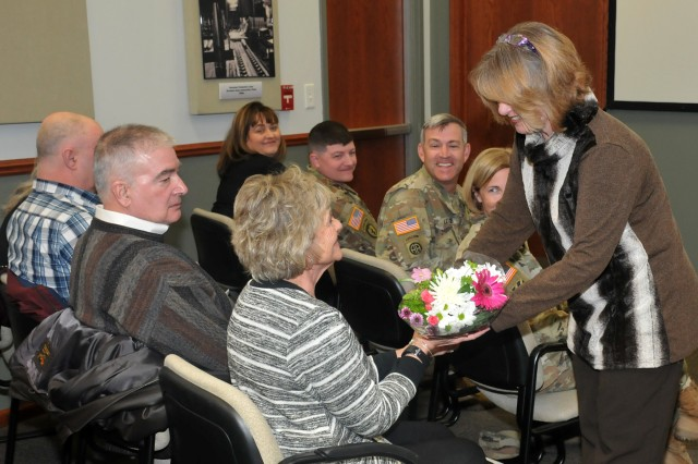 A JMC staff member presents flowers to Command Sgt. Maj. Morrison's mom, Mary Nesbitt, during the JMC Assumption of Responsibility Ceremony, March 18.