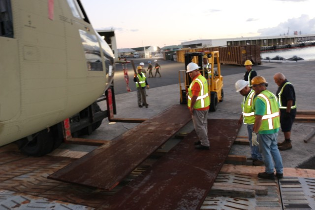 Transporters from FLC-Pearl Harbor and the 599th Transportation Brigade add steel plates to the ramp and buttress them with boards to avoid damaging helicopters as they are offloaded during port operations at Pearl Harbor on March 14.