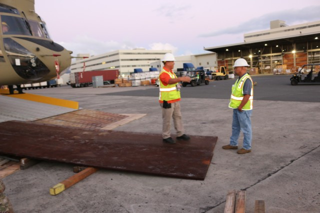 Earl Fernandes, FLC-Pearl Harbor, and Frank Viray, 599th Transportation Brigade, discuss the operation as they bring in more steel plates to lower the angle of the Cape Orlando's stern ramp to avoid damaging helicopters as they are offloaded during port operations at Pearl Harbor on March 14.
