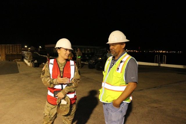 Sgt. 1st Class Jennifer Berger, 25th Infantry Division Transportation Office NCOIC, and Frank Viray, 599th Transportation Brigade traffic management specialist, discuss the operation during cargo offload at Pearl Harbor on March 14.