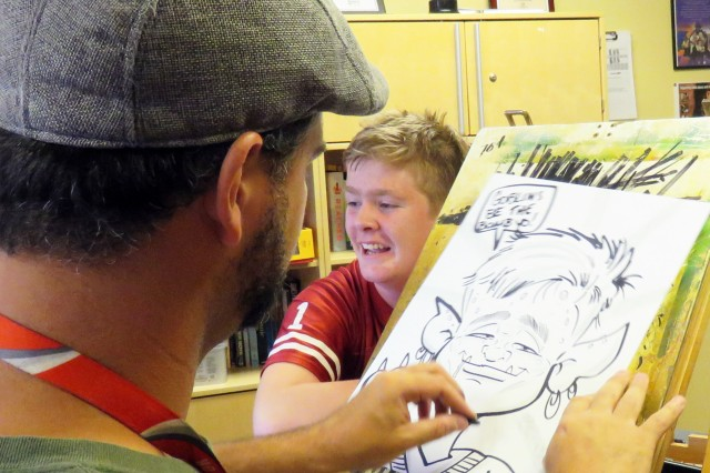 "Illustrator Jason Gerke, also known as ""The Doodler,"" draws a caricature for a Fort McCoy summer camper Aug. 30, 2018, at Child and Youth Services' School Age Center/Youth Center. This photo earned a third-place finish in the feature photo category for the 2018 Installation Management Command Keith L. Ware Communications Awards. (U.S. Army photo by Aimee Malone, Public Affairs Office, Fort McCoy, Wis.)"