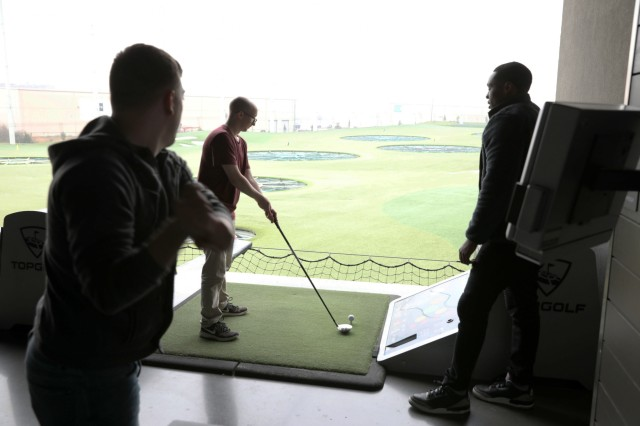 Spc. Charles Mickey (left) and Darren Massey (right) with Signal Intelligence Sustainment Company, Headquarters and Headquarters Battalion, 101st Airborne Division (Air Assault) coach their fellow Soldier on the proper mechanics for hitting a golf ball at Topgolf Nashville during the Strong Bonds single Soldiers retreat March 8, 2019. One of the games the Soldiers played at the driving range was longest drive where Soldiers took turns aiming for the farthest out targets to see who got the top score. (U.S. Army photo by Spc. Jeremy Lewis) (This photo had levels adjusted to enhance the subject)
