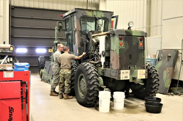 """Students in the 91L10 Construction Equipment Maintenance Repairer Course work together to take an engine out of a grader Feb. 20, 2019, during training at Fort McCoy's Regional Training Site-Maintenance facility at Fort McCoy, Wis. The completion of the course provided the students with certification in the Army's """"91-Lima"""" career field - construction equipment repairer. According to the Army, construction-equipment repairers are responsible for maintaining trucks, bulldozers, power shovels, and other heavy equipment needed for construction operations. (U.S. Army Photo by Scott T. Sturkol, Public Affairs Office, Fort McCoy, Wis.)"""