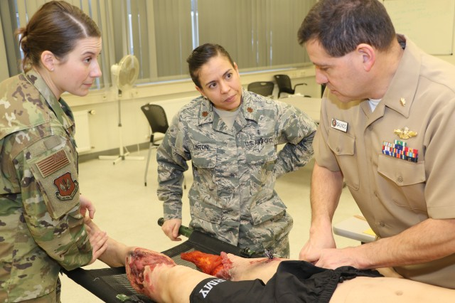 Navy Cmdr. Roger Galindo, general surgeon at Navy Hospital Naples in Italy, demonstrates the proper management of extremity trauma to certified registered nurse anesthetists Air Force Maj. Lindsey Marquez (left), and Maj. Jessica Linton during the Advanced Trauma Life Support training at Landstuhl Regional Medical Center Mar. 15. ATLS is a required certification for critical care and trauma providers and is currently only offered at LRMC for military medical professionals assigned to the U.S. Europe Command, U.S. Africa Command and U.S. Central Command.