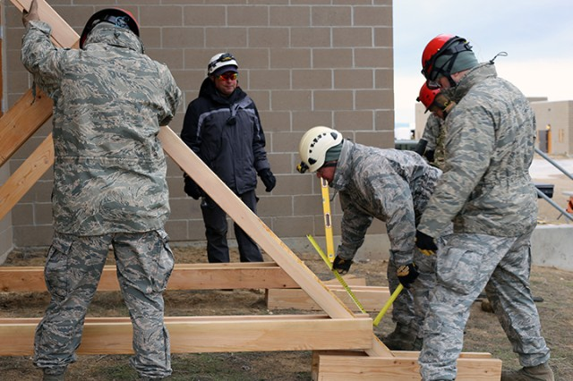 Members of the search and extraction team work together to brace a wall. During a major catastrophe search and extraction, personnel is trained in bracing buildings that are at risk or collapse to extract remains. The team can evaluate a building and build bracing on the scene.