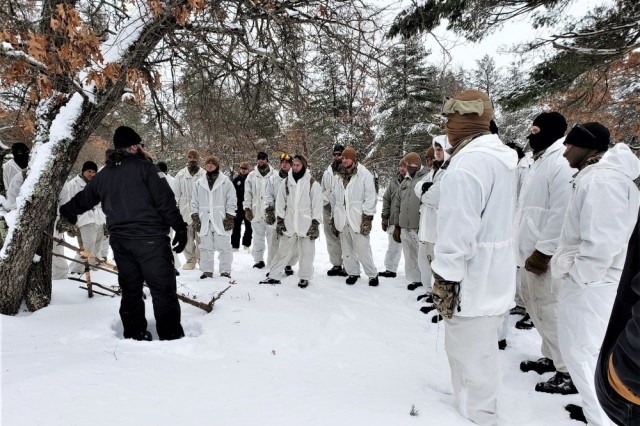 Students in the Cold-Weather Operations Course (CWOC) Class 19-05, which included many Soldiers from the 75th Ranger Regiment, listen to CWOC Instructor Hunter Heard discuss improved shelters Feb. 23, 2019, at Fort McCoy, Wis. CWOC students are trained on a variety of cold-weather subjects, including skiing and snowshoe training as well as how to use ahkio sleds and other gear. Training also focuses on terrain and weather analysis, risk management, cold-weather clothing, developing winter fighting positions in the field, camouflage and concealment, and numerous other areas that are important to know in order to survive and operate in a cold-weather environment. The training is coordinated through the Directorate of Plans, Training, Mobilization and Security at Fort McCoy.