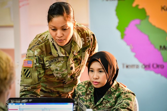 U.S. Army Lt. Col. Angela Gentry, Washington Army National Guard, discusses battle drills with her Malaysian army counterpart, Maj. Nurkhairunisa, during Exercise Bersama Warrior in Malaysia, March 10, 2019. Bersama Warrior is a joint bilateral exercise between the Malaysian Armed Forces and the United States military. The exercise focuses on planning and conducting joint and coalition peace enforcement operations and is held in Kuala Lumpur from March 7-15, 2019.