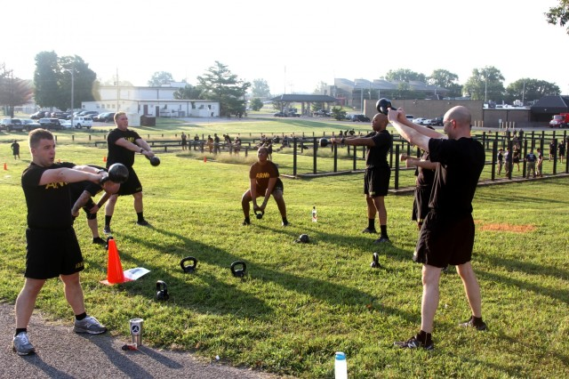 Soldiers from the Judge Advocate General Corps perform kettlebell swings during circuit training behind Olive Gym on Fort Campbell, Kentucky, July 27. The circuit training consisted of nine lanes and teams rotated through each during morning physical training. (US Army Photo by Pfc. Lynnwood Thomas, 40th Public Affairs Detachment)