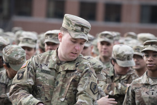 1st Sgt. Glenn Riddell, U.S. Army Human Resources Command HHC first sergeant,replaces his historical minuteman patch with the redesigned shoulder sleeve insignia during a re-patching ceremony held at the Lt. Gen. Timothy J. Maude complex located on Fort Knox, Ky., March 20, 2019. The updated patch features a modern day Soldier, standing in full gear and bearing a weapon, ready to support the Army mission. The globe surrounding the Soldier represents HRC's worldwide mission and the four stars signify the four components of the Army: Active, Guard, Reserve, and Civilian. (U.S. Army photo by Master Sgt. Brian Hamilton/released)