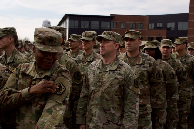 U.S. Army Human Resource Command Soldiers replace their historical Minuteman patches with the redesigned unit patch.  The updated patch features a modern day Soldier, standing in full gear and bearing a weapon, ready to support the Army mission.   The globe surrounding the Soldier represents HRC's worldwide mission and the four stars signify the four components of the Army: Active, Guard, Reserve, and Civilian. (U.S. Army photo by Nicole Hawk)