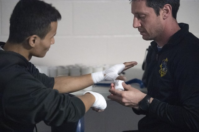 A boxer gets his hands taped before the 8th annual boxing extravaganza March 16 at the Solomon Center. Sixteen amateur pugilists showed off their skill during the event.
