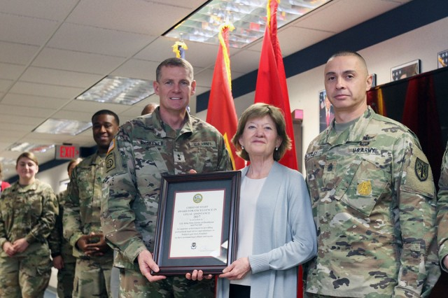 Kathryn McClure, Client Services chief, accepts the 2017 Army Chief of Staff Award for Excellence in Legal Assistance, from Fires Center of Excellence and Fort Sill Commanding General Maj. Gen. Wilson A. Shoffner and Command Sgt. Maj. John Foley March 12, 2019, at the Fort Sill Welcome Center.