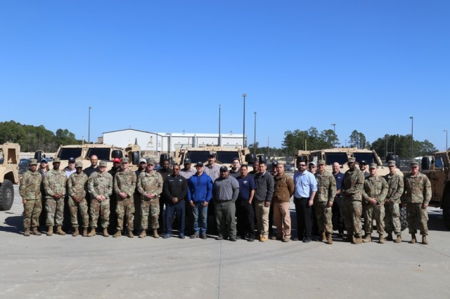 Soldiers from the 1st Armored Brigade Combat Team, 3rd Infantry Division and the team from Oshkosh Defense pose in front of the first Joint Light Tactical Vehicles (JLTV) that were delivered to the battalions, Jan. 28.