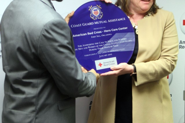 Retired Coast Guard Rear Adm. Cari Thomas, right, CEO of Coast Guard Mutual Assistance Inc., presents Joshua Williams, manager of the American Red Cross Hero Care Center on Fort Sill, with an award for its partnership that provided millions of dollars in assistance to Coast Guardsmen and their families during the 35-day government shutdown, March 13, 2019.