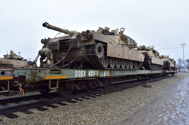 A Soldier secures an M1 series Abrams main battle tank to a rail car during railhead operations. Railhead operations are a critical element of sustainment at the brigade combat team level in decisive action.