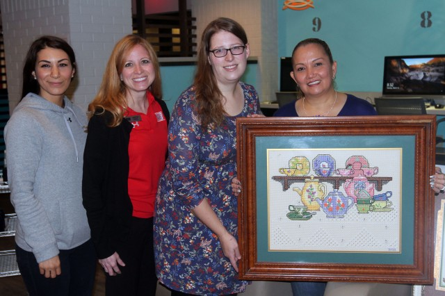 """The staff of the Fort Sill USO Center welcomes Ella Foley as she prepares to teach the art of cross-stitching at their monthly """"Coffee Connections"""" series for military spouses. From left are Hasi Jackson, USO center operations supervisor; Jennifer Kirby, senior director of USO Oklahoma; Jenn Troxell, USO operations and programs manager, and Ella Foley with one of her completed projects."""