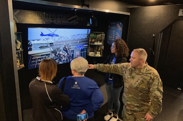 Sgt. 1st Class Richard Sullins, STEM mobile exhibit operator with Mission Support Battalion, explains the technological advancements for the future Soldier during a video presentation inside the STEM mobile exhibit.