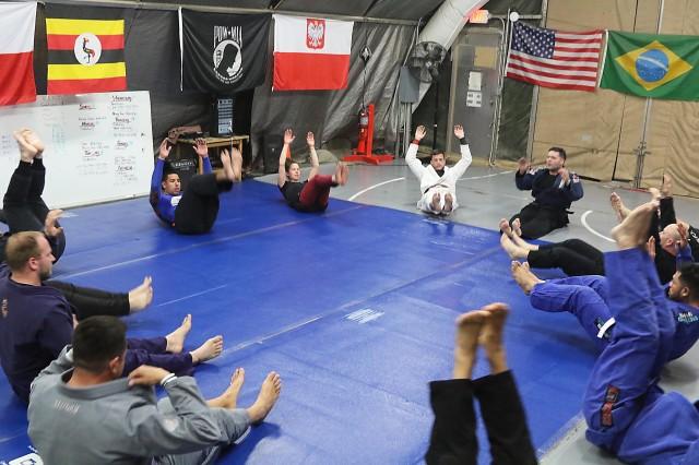 Members of the Bagram Airfield Brazilian Jiu-Jitsu team warm up with core exercises at Bagram Airfield, Afghanistan.