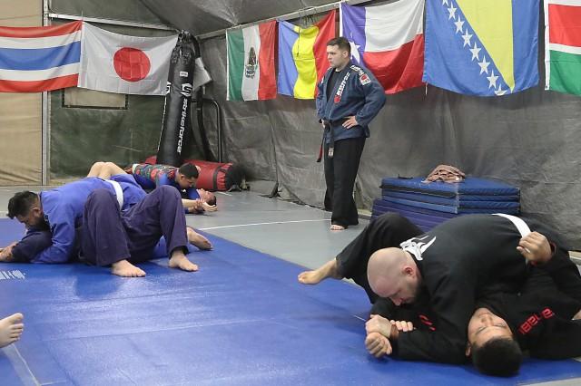 Members of the Brazilian Jiu-Jitsu class at Bagram Airfield, Afghanistan, practice the americana shoulder lock as Brandon Gaskins, Air Force service member, observes at Bagram Airfield, Afghanistan.