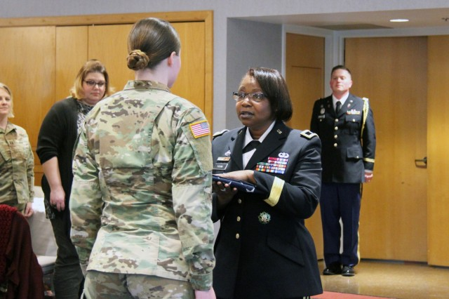 Brig. Gen. Twanda Young (right), deputy commanding general for the U.S. Army Human Resources Command, gives a flag to Sgt. Christine Meyers with the Fort McCoy Army Health Clinic during the Women's History Month observance March 14, 2019, at McCoy's Community Center. Young was the guest speaker. (U.S. Army Photo by Aimee Malone, Public Affairs Office, Fort McCoy, Wis.)