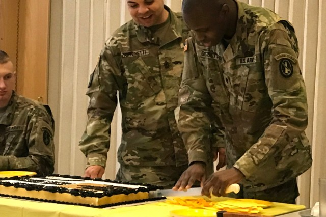 (Left to right) 1st Sgt. Jonathan Antonetti, the first sergeant of Headquarters and Headquarters Company, and Spc. Nealis Giggetts, JBM-HH Dining Facility, cut the cake during the March 14 Army Emergency Relief kickoff.