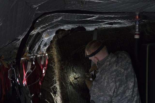 Army National Guard Soldiers strap in a hay bale in an aircraft. The aircraft can fit 3 hay bales in it.