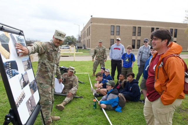 Sgt. Christian Aracena, a Horizontal Construction Engineer 61st Quartermaster Battalion, explains a weapon system to scouts in Troop 533 on March 23, 2019 during their visit to Fort Hood, Texas. The 61st Quartermaster Battalion hosted 61 Boy Scouts in Troop 533 from Cypress, Texas who spent the weekend at Fort Hood, Texas to spend time with Soldiers and experience what they do.