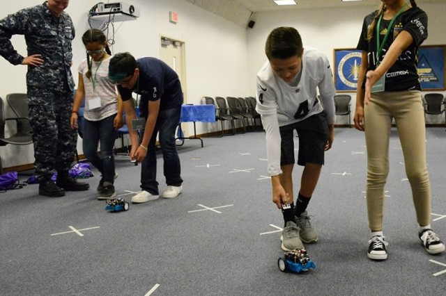 """GEMS I middle school students learn to navigate robots during GEMS camp in 2017. One student provided the commands and the student controlling the robot followed the commands. The goal of the exercise was to get the robot to the other side of the room without hitting the """"X"""" marks on the floor."""