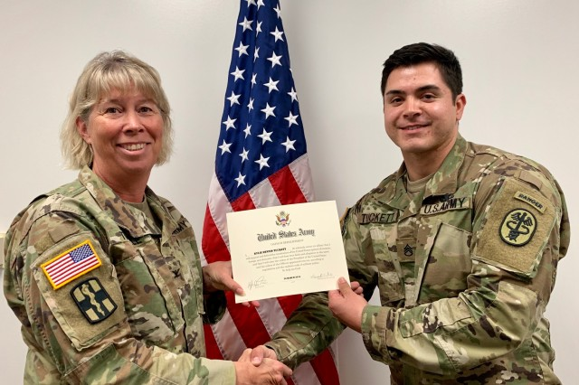 Regional Health Command-Pacific Chief of Staff Col. Laura Trinkle presents Staff Sgt. Kylie Tuckett, from Tripler Army Medical Center, his reenlistment certificate on March 26, 2019. Tuckett, accepted into the Green to Gold program, will transfer from TAMC to begin the senior Reserve Officers' Training Corps program at the University of Wyoming. This reenlistment will take him through his ROTC program until he becomes a commissioned officer.