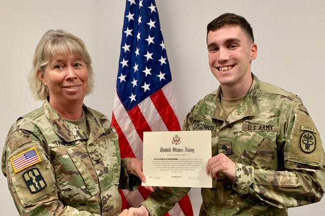 Regional Health Command-Pacific Chief of Staff Col. Laura Trinkle presents Sgt. David Furstenberg his reenlistment certificate at the regional headquarters in Honolulu on March 26, 2019. Furstenberg, accepted into the Green to Gold program, will transfer from RHC-P to begin the senior Reserve Officers' Training Corps program at the University of Wyoming. This reenlistment will take him through his ROTC program until he becomes a commissioned officer.