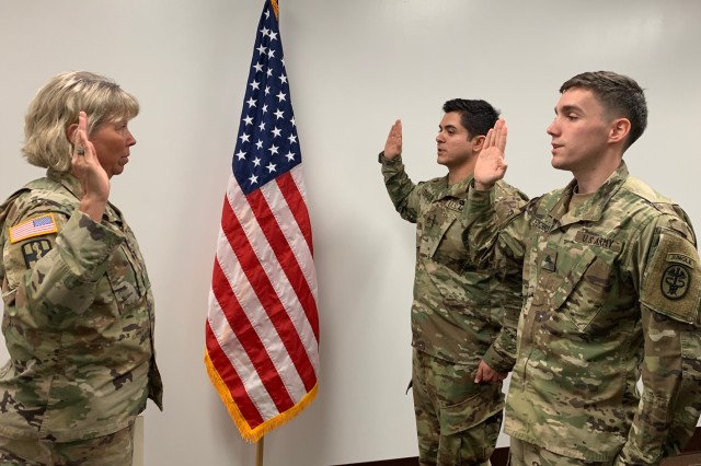 Staff Sgt. Kylie Tuckett (center), from Tripler Army Medical Center, and Sgt. David Furstenberg (right), from Regional Health Command-Pacific, reenlist together by RHC-P Chief of Staff Col. Laura Trinkle at the regional headquarters in Honolulu on March 26, 2019. Furstenberg and Tuckett were both accepted into the Green to Gold program and will begin the senior Reserve Officers' Training Corps program at the University of Wyoming in August. This enlistment will take them through their ROTC program until they become commissioned officers.