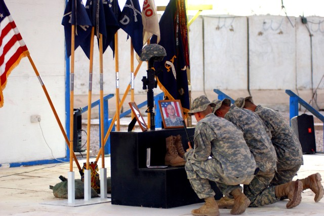 Soldiers kneel to pay their respects during a memorial ceremony June 7, 2007 at Camp Striker for Staff Sgt. Travis Atkins, who was killed June 1, 2007 by a suicide bomber near Sadr Al-Yusufiyah, Iraq. Atkins was on patrol with his unit, D Company, 2nd Battalion, 14th Infantry Regiment, 2nd Brigade Combat Team, 10th Mountain Division (LI), when they detained men who were wearing suicide vests.