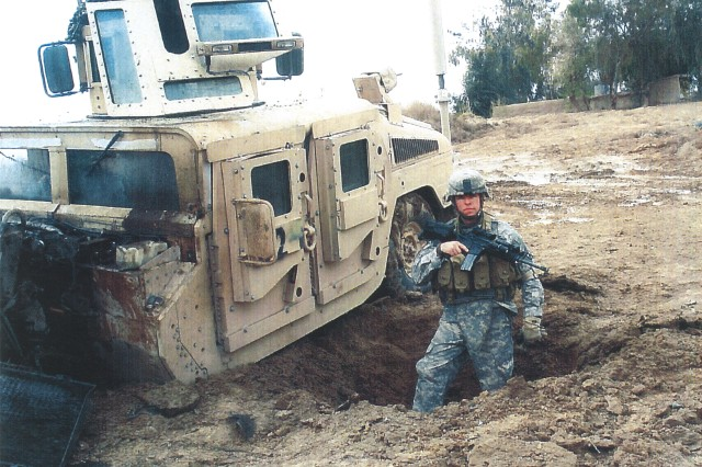 Sgt. Travis Atkins stands next to his vehicle after it was damaged by an improvised explosive devise in Iraq during 2007.