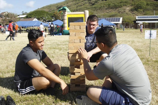 SPC Jamil Malapit (left) SPC Amron Hendley (center) and PFC Justin Kwon (right), build commradery while dismantling a tower of wooden blocks in a giant game of Jenga. (Army Photo by Staff Sgt. John Portela)