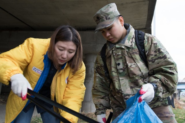 Spc. Estela Valdovinos, native of Monticello, Florida, Camp Casey Soldier, collects debris alongside Choi, Misun, Dongducheon City volunteer, during the 2019 Shincheon Riverside Cleanup, Dongducheon, Republic of Korea, March 21, 2019. Camp Casey Soldiers and Dongducheon volunteers removed trash and debris from Shincheon River as part of the Good Neighbor Program. (U.S. Army photo by Sgt. Osvaldo Martinez)