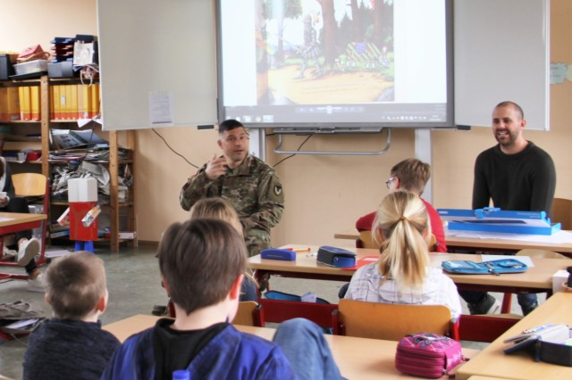 Col. Jason T. Edwards, U.S. Army Garrison Rheinland-Pfalz commander, reads a story to the children of Göttschied Elementary School in Idar-Oberstein, Germany, March 26. The commander read to the students, while his wife, Jackie, taught a cardio workout class to third and fourth graders.