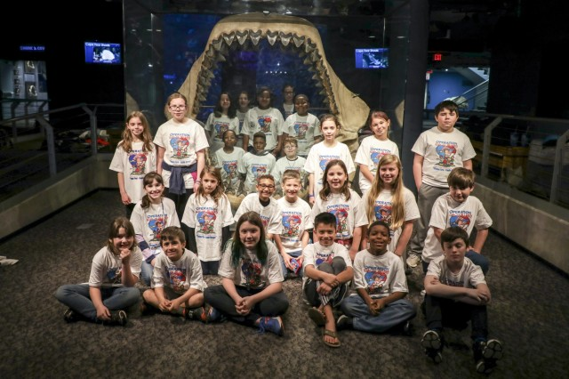 Children of North Carolina National Guardsmen gather around a replica of a Megalodon Shark jaw at the aquarium where they will be sleeping during the Sleeping With the Fishes event March 23, 2019, at the North Carolina Aquarium at Fort Fisher. The event was sponsored by Kids on Guard, a non-profit organization that supports the North Carolina National Guard Family Programs and hopes to give Guard children a chance to bond with other kids in similar situations.