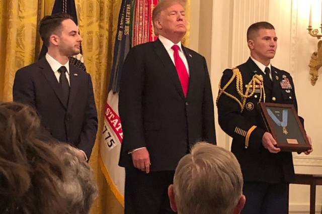 President Trump presents the Medal of Honor to Trevor Oliver, the son of the late Staff Sgt. Travis Atkins. Atkins sacrificed his life by smothering his body over a suicide bomber to save three Soldiers. Trump honored Atkins during a White House ceremony March 27, 2019.