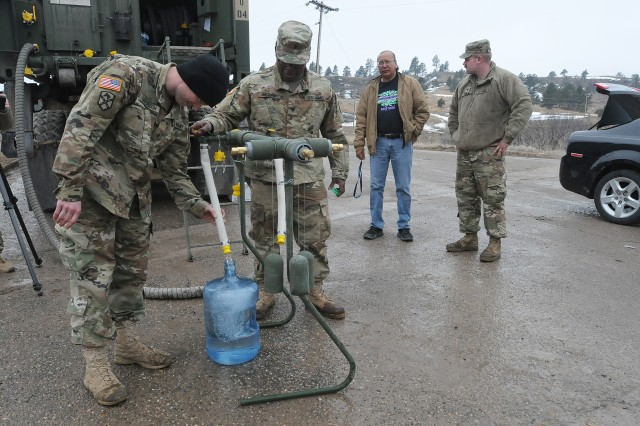 U.S. Army Sgt. Seth Greenough, left, and Spc. Roderick McRae, center, and Spc. Baily Toering, members of Company A, 139th Brigade Support Battalion, South Dakota Army National Guard, provide drinkable water to a resident of Porcupine, S.D, on the Pine Ridge Reservation, March 25, 2019. Thirteen SDARNG Soldiers were activated for state duty in Pine Ridge after a county waterline failed due to extreme flooding leaving residents in seven communities without water in their homes.