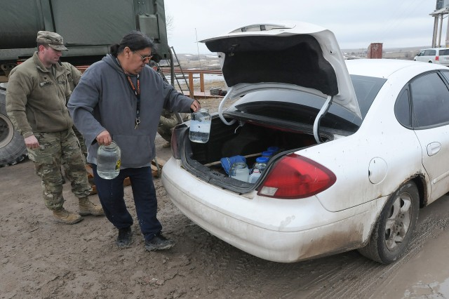 Lester Rowland loads containers of drinkable water into his car with the help of U.S. Army Spc. Tracy Lennick, Company A, 139th Brigade Support Battalion, South Dakota Army National Guard, at Sharps Corner on the Pine Ridge Reservation, March 25, 2019. Thirteen SDARNG Soldiers were activated for state duty in Pine Ridge after a county waterline failed due to extreme flooding leaving residents in seven communities without water in their homes.