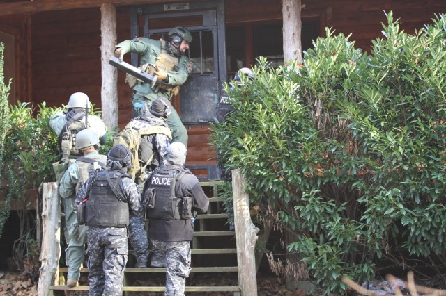 Members of 'Strike Team 2' breach a door as part of a search warrant operation during an inter-agency training Nov. 27, at the Public Safety Training Center in Clarksville, Tenn. The strike team included members of the 163rd Military Police Department Special Reaction Team, the Montgomery County Sheriff's Office Emergency Services Unit and the Clarksville Police Department. The two agencies met to compare civilian and military policing techniques.
