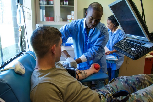 FORT BENNING, Ga. -- Staff Sgt. Jemiah Daniels, center, a lab technician with the Sullivan Memorial Blood Center, swabs iodine onto the arm of Pvt. Tyler Griggs, an Infantry Soldier, in preparation of drawing blood from Griggs. Military and civilian staff of the Sullivan Memorial Blood Center located at Fort Benning briefed Maneuver Center of Excellence Commanding General Maj. Gen. Gary M. Brito on the center's contributions and capabilities in relation to the Armed Services Blood Program during his visit to the facility March 22, 2019. The ASBP is the official blood collection, manufacturing and transfusion program for the U.S. military, and provides blood products and services for all worldwide customers in both peace and war. (U.S. Army photo by Megan Garcia, Fort Benning Maneuver Center of Excellence Public Affairs)