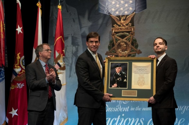 Secretary of the Army Mark T. Esper (middle) presents a memorial plaque of the late Staff Sgt. Travis Atkins to his son, Trevor Oliver, as Acting Deputy Secretary of Defense David Norquist looks on. Atkins was posthumously inducted into the Pentagon's Hall of Heroes during a ceremony at the Pentagon March 28, 2019. President Trump presented the Medal of Honor to Atkins' family on March 27.