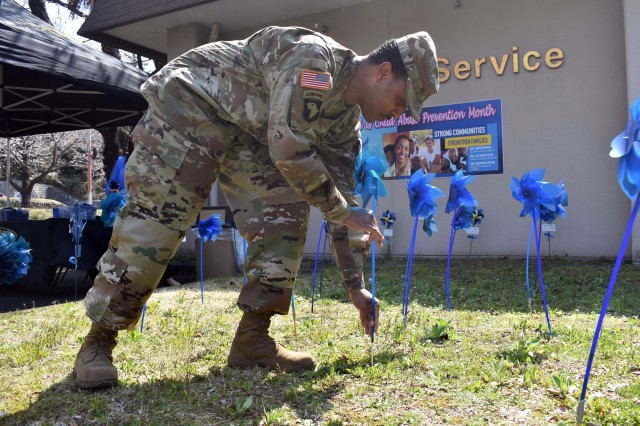 Staff Sgt. Dnard Edwards, a member of the U.S. Army Japan Band, plants a pinwheel for Child Abuse Awareness Month at Camp Zama Army Community Service March 27.