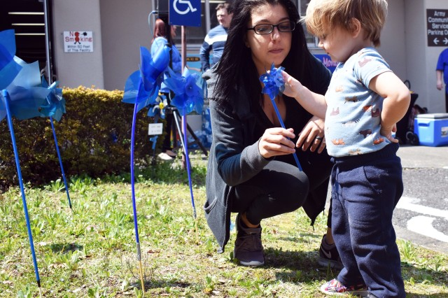 Rayanna Sherman hands her son John, 21 months old, a pinwheel during the Plant a Pinwheel for Child Abuse Awareness Month event at Camp Zama Army Community Service March 27.