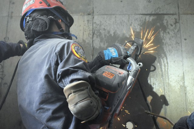 A U.S. military firefighter uses a saw to breach a concrete wall during training at Camp Zama March 26. The training was a part of the 33rd annual U.S. Forces Japan Fire Officers Association Training Symposium.