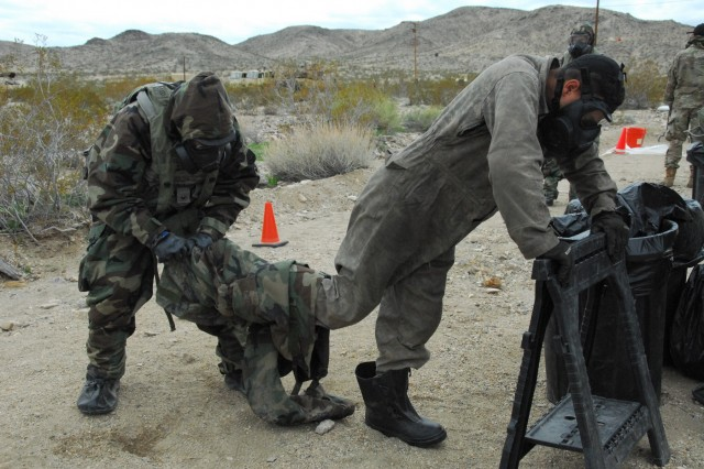 One Soldier from the 44th Chemical Company, Fort Bliss, Texas, helps another Soldier remove his uniform at a field decontamination station during the March training rotation at the National Training Center, Fort Irwin, California. The Soldiers, attached to the 83rd Chemical, Biological, Radiological, Nuclear Battalion from Fort Stewart, Georgia, and the 2nd Brigade Combat Team of the 1st Infantry Division, Fort Riley, Kansas, spent 14 days in the Mojave Desert working together in various chemical and biological operations such as personnel decontamination.