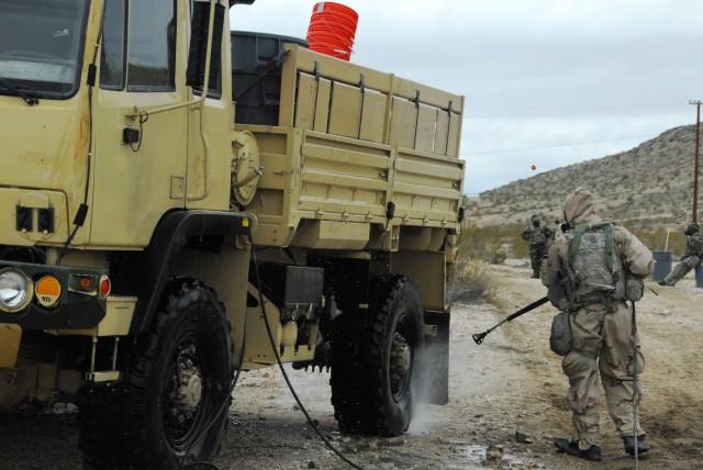 Soldier sprays water to decontaminate truck