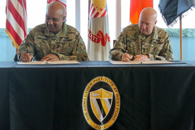 Lt. Gen. Darryl A. Williams, Superintendent of the U.S. Military Academy, and Maj. Gen. Peter A. Bosse, Commanding General of 335th Signal Command, sign a memorandum of agreement between The Army Cyber Institute at West Point and the 335th Signal Command's Army Reserve Cyber Operations Group. The memorandum formalizes a partnership between ACI and the 335th for 10 reserve Soldiers to work alongside active duty Soldiers to improve the Army's cyber capabilities. (U.S. Army photo by Brandon O'Connor)