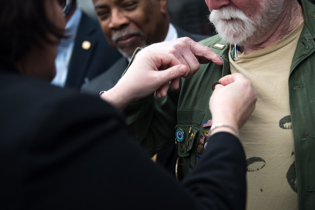 Kim Joiner, the acting principal deputy assistant to the secretary of defense for public affairs, pins a Vietnam Veteran lapel pin on a veteran during an observance of Vietnam War Veterans Day at the Vietnam War Memorial in Washington, March 29, 2019.